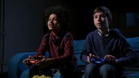Усмехаясь подростки играя видеоигры дома акции видеоматериалы
