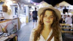 Усмехаясь девушка идя через рынок ночи видеоматериал