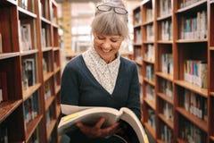 Усмехаясь старшая женщина смотря положение книги в библиотеке стоковые изображения