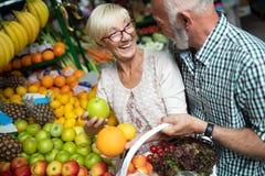 Усмехаясь старшие пары держа корзину с овощами на рынке стоковое изображение