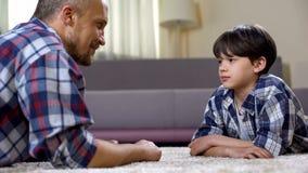 Усмехаясь сын смотря сына, лежа на поле, беседы людей, доверительные отношения стоковые изображения