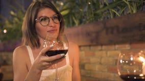 Усмехаясь удерживание женщины в бокале руки красном и говорить на выравнивать обедающий Счастливая женщина выпивая красное вино н видеоматериал
