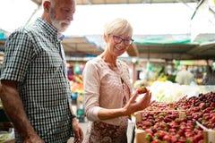 Усмехаясь овощи старших пар покупая и на merket стоковая фотография rf