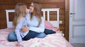 Усмехаться босоногого ребенка говоря и обнимать с молодой милой женщиной сидя на кровати в спальне сток-видео