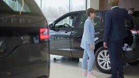 Успешная стильная пара дела выбирает новый автомобиль в роскошном мотор-шоу Выставочный зал автомобиля видеоматериал