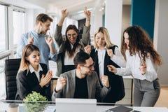 Успешные молодые бизнесмены поднимают руки в кулаках и кричащий со счастьем пока работающ с компьютером в деле стоковые изображения rf