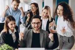 Успешные молодые бизнесмены поднимают руки в кулаках и кричащий со счастьем пока работающ с компьютером в деле стоковое изображение rf