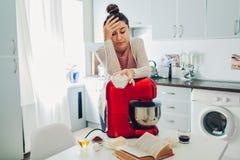 Уставшая домохозяйка полагаясь на кухонном комбайне пока варящ на кухне Осложненный рецепт стоковые фото