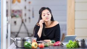 Уставшая стильная молодая азиатская женщина варя свежую еду имея съемку головной боли среднюю акции видеоматериалы