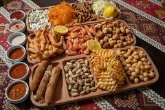 Установите закусок пива, 11 разнообразий и 6 соусов на деревянном столе со скатертью с национальными картинами стоковые фотографии rf