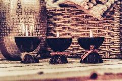 Уютное домашнее оформление интерьера, горящие свечи на пестротканом половике на предпосылке плетеной коробки соломы - изображении стоковые изображения rf