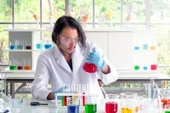 Ученый проверяя жидкостное вещество на лаборатории стоковое фото