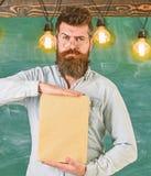 Учитель в eyeglasses представляя пустую книгу Бородатый битник держит книгу, доску на предпосылке словесность стоковое фото