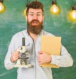 Учитель в eyeglasses держит книгу и микроскоп Концепция науки Ученый держит книгу и микроскоп, доску дальше стоковое фото