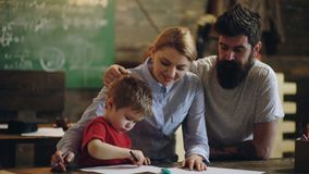 Урок в чертеже Маленький ребенок учит чертеж на бумаге Женщина и человек дают урок мальчика в чертеже Я люблю нарисовать Семья акции видеоматериалы