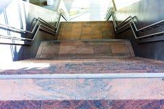 Шаги водя к подвалу Мраморные лестницы от нескольких уровней Gelenders металла рядом с лестницами стоковое изображение