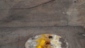 Шар smoothie банана с плодом дракона, манго, granola, изюминкой, кусками миндалины, и семенами chia на деревянной предпосылке видеоматериал