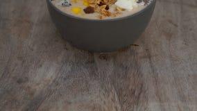 Шар smoothie банана с плодом дракона, манго, granola, изюминкой, кусками миндалины, и семенами chia на деревянной предпосылке сток-видео