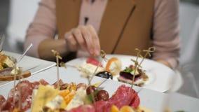 Шведский стол события Женщина кладет дальше ее канапе плиты различные 4K медленный mo видеоматериал