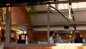 ШЕФФИЛД, ВЕЛИКОБРИТАНИЯ - 9-ОЕ ДЕКАБРЯ 2019: Белая женщина делает заказ на полинянный - работы столового прибора стоковая фотография rf