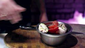 Шеф-повар брызгает соль на салате овощей и подготавливает его для выпуска в ресторане акции видеоматериалы