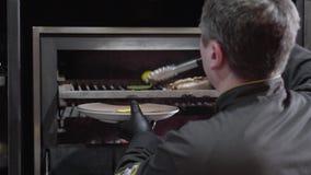 Шеф-повар в черных перчатках вытягивает из горячего гриля печи как раз сварил болгарский перец, накаленные докрасна перцы chili и видеоматериал