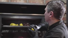 Шеф-повар в черных перчатках кладя в горячий гриль печи отрезал части corns к зажаренный им от всех сторон конец вверх видеоматериал