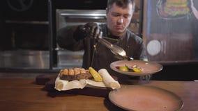 Шеф-повар в черных перчатках служа на древесине как раз сварил очень вкусных сочных рыб с зажаренными болгарскими перцами, перца  видеоматериал