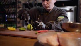 Шеф-повар прерывая с известкой острого ножа на деревянной доске для подготовки салата в большой плите видеоматериал