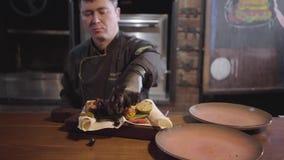 Шеф-повар профессии ресторана в особенной черной форме служит плита рыб зажаренных семгами с зажаренными овощами сток-видео