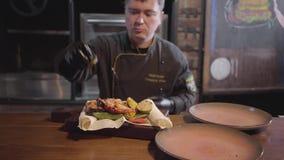 Шеф-повар профессии ресторана в особенной черной форме служит плита рыб зажаренных семгами с зажаренными овощами видеоматериал