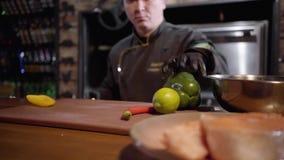 Шеф-повар портрета прерывая с зеленым цветом острого ножа и желтым болгарским перцем на деревянной доске для подготовки салата в  видеоматериал
