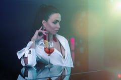 Шикарная женщина брюнета с коктейлем в баре стоковое фото rf