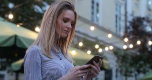Шикарная кавказская белокурая женщина печатает по ее телефону с выравниваясь светами на предпосылке, конце-вверх видеоматериал