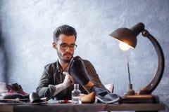 Шикарный приятный бородатый мастер проверяя подошву ботинок стоковое фото