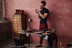 Шикарный приятный сапожник держа ботинок стоковая фотография rf