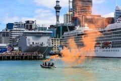 Шлюпка демонстрируя оранжевый морской пирофакел в гавани Окленда, Новой Зеландии стоковое фото