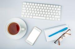 Таблица стола офиса с клавиатурой компьютера, смартфоном, чашкой чаю стоковое фото rf