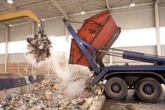 Тележка сбрасывает отход к мусоросжигателю, отверстие где большой самосхват принять хлам и положить ее в огонь Весь отход обрабат стоковое фото