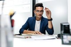 Темн-с волосами молодой архитектор в стеклах и в синем пиджаке работает с документами на столе в офисе стоковые изображения