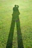Тень человека на предпосылке зеленой травы иллюстрирует концепцию фотографа стоковое изображение rf