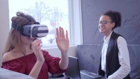 Технология VR, жизнерадостные мульти-этнические девушки использует стекла VR и современную компьютерную технологию для виртуально акции видеоматериалы