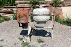 Тяжело - используемый побитый вниз заржаветый смеситель металла электрический конкретный поверх кучи гравия с большими деревянным стоковое фото rf