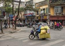 Тяжело нагруженный мотоцикл путешествуя на улице в Ханое, Вьетнаме стоковые фото