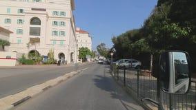 Туристический автобус управляет в улицах Гибралтара Беседы туристического гида об осмотр достопримечательностей объектах Взгляд ч акции видеоматериалы