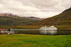 Туристическое судно в фьорде Sejdisfjordur, Исландии Океанский лайнер в гавани моря на ландшафте горы Курсировать для удовольстви стоковое фото rf