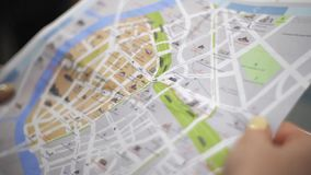 Туристская исследуя карта города навигации и сравнивает с картой метро Крупный план Fpv акции видеоматериалы