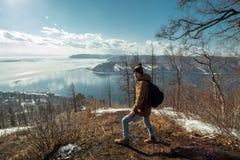 Туристский путешественник со стойками рюкзака на горе и взглядами на красивом виде Lake Baikal зима температуры России ландшафта  стоковое изображение