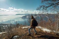 Туристский путешественник со стойками рюкзака на горе и взглядами на красивом виде Lake Baikal зима температуры России ландшафта  стоковая фотография