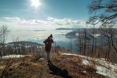 Туристский путешественник со стойками рюкзака на горе и взглядами на красивом виде Lake Baikal зима температуры России ландшафта  стоковые изображения